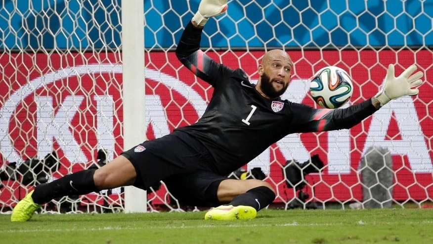 FILE - In this July 1, 2014, file photo, United States' goalkeeper Tim Howard saves a shot by Belgium during a World Cup round of 16 soccer match at the Arena Fonte Nova in Salvador, Brazil. Howard has won the 2014 Player of the Year award on Thursday, Dec. 4, 2014, for his work with the U.S. national team. It is the first time Howard has won the prestigious honor given to a U.S. team member by Futbol de Primera.  (AP Photo/Felipe Dana, File)