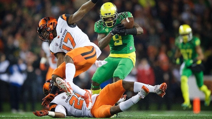 Oregon quarterback Marcus Mariota (8) scores a touchdown against Oregon State during the third quarter of an NCAA college football game in Corvallis, Or., Saturday, Nov. 15, 2014. (AP Photo/Troy Wayrynen)
