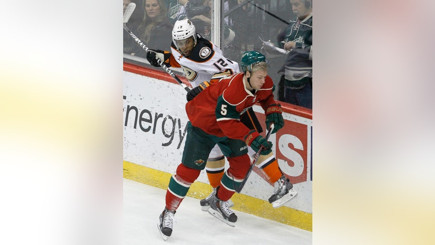 Minnesota Wild defenseman Christian Folin (5) checks Anaheim Ducks right wing Devante Smith-Pelly (12) into the boards during the first period of an NHL hockey game in St. Paul, Minn., Friday, Dec. 5, 2014. (AP Photo/Ann Heisenfelt)