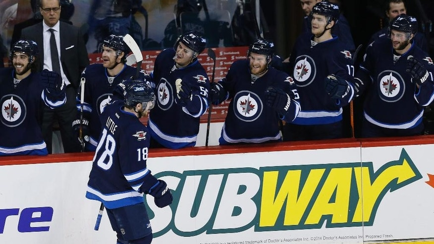 Winnipeg Jets' Bryan Little (18) and the Jet's bench celebrate Little's third goal of the game against the Colorado Avalanche during third-period NHL hockey game action in Winnipeg, Manitoba, Friday, Dec. 5, 2014. (AP Photo/The Canadian Press, John Woods)