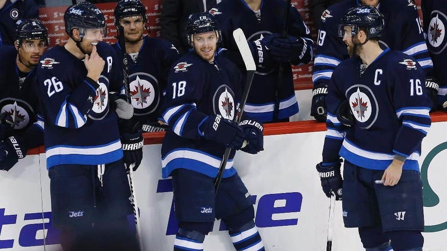 A hat is tossed from the crowd as Winnipeg Jets' Blake Wheeler (26), Bryan Little (18) and Andrew Ladd (16) celebrate Little's third goal of the game against the Colorado Avalanche during third-period NHL hockey game action in Winnipeg, Manitoba, Friday, Dec. 5, 2014. (AP Photo/The Canadian Press, John Woods)
