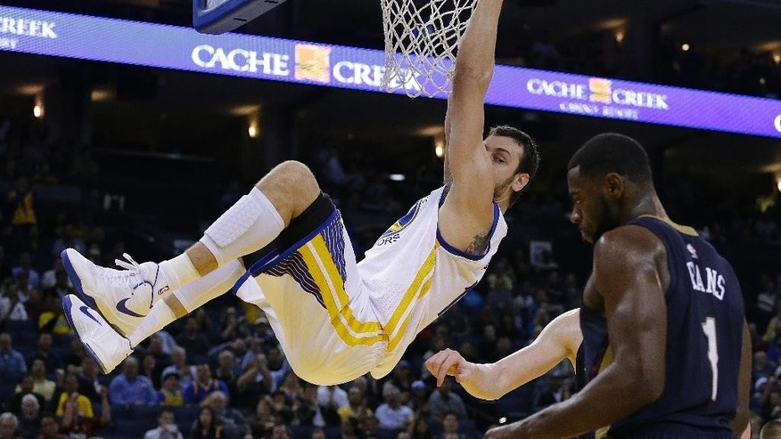 Golden State Warriors' Andrew Bogut hangs on the rim after scoring against the New Orleans Pelicans during the second half of an NBA basketball game Thursday, Dec. 4, 2014, in Oakland, Calif. At right is New Orleans' Tyreke Evans (1). (AP Photo/Ben Margot)