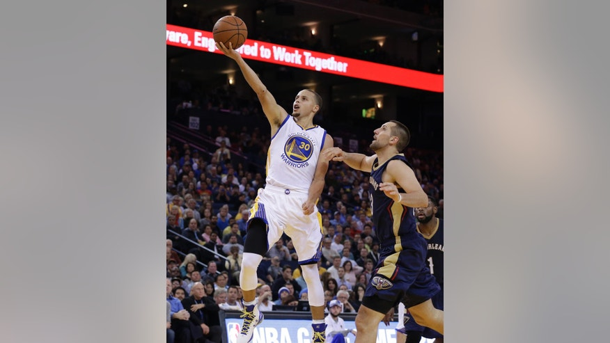 Golden State Warriors' Stephen Curry (30) lays up a shot over New Orleans Pelicans' Ryan Anderson, right, during the second half of an NBA basketball game Thursday, Dec. 4, 2014, in Oakland, Calif. (AP Photo/Ben Margot)
