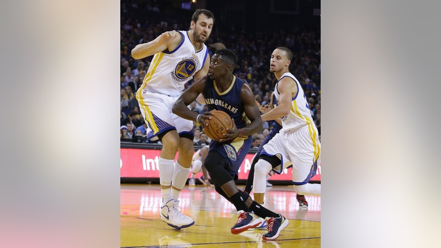 New Orleans Pelicans' Tyreke Evans, center, drives the ball between Golden State Warriors' Andrew Bogut, left, and Stephen Curry during the first half of an NBA basketball game Thursday, Dec. 4, 2014, in Oakland, Calif. (AP Photo/Ben Margot)