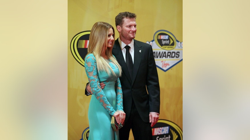 Dale Earnhardt Jr., right, and his girlfriend Amy Reimann stand on the red carpet prior to the NASCAR Sprint Cup Series Awards at Wynn Las Vegas hotel-casino Friday, Dec. 5, 2014, in Las Vegas. (AP Photo/Ronda Churchill)