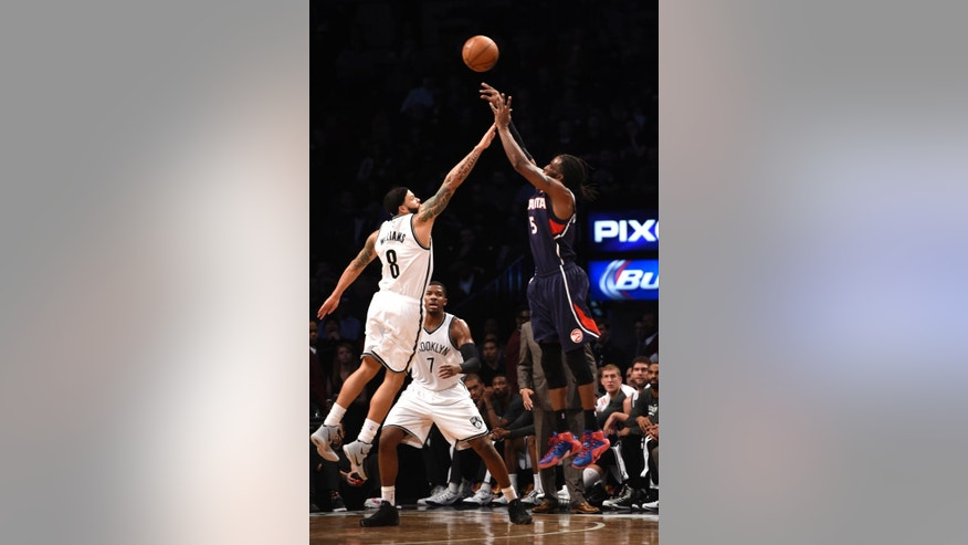 Atlanta Hawks forward DeMarre Carroll (5) shoots a three pointer over Brooklyn Nets guard Deron Williams (8) as forward Joe Johnson (7) looks on just before the end of the first half of an NBA basketball game at Barclay's Center on Friday, Dec. 5, 2014, in New York. (AP Photo/Kathy Kmonicek)