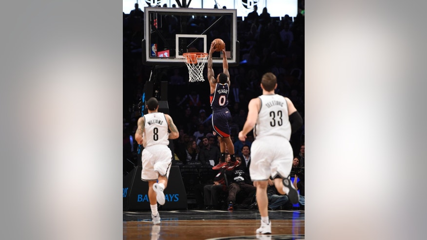Brooklyn Nets guard Deron Williams (8) and forward Mirza Teletovic (33) run down court as they watch Atlanta Hawks guard Jeff Teague (0) dunk a basket after turning over the ball in the first half of an NBA basketball game at Barclay's Center on Friday, Dec. 5, 2014, in New York. (AP Photo/Kathy Kmonicek)