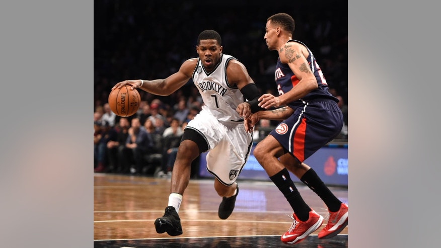 Brooklyn Nets forward Joe Johnson (7) drives the ball around Atlanta Hawks guard Thabo Sefolosha (25) in the first half of an NBA basketball game at Barclay's Center on Friday, Dec. 5, 2014, in New York. (AP Photo/Kathy Kmonicek)