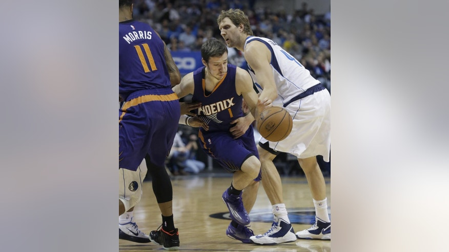 Phoenix Suns guard Goran Dragic (1) drives past a grabbing Dallas Mavericks forward Dirk Nowitzki (41) during the first half of an NBA basketball game Friday, Dec. 5, 2014, in Dallas. (AP Photo/LM Otero)