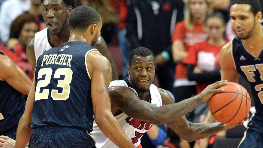 Louisville's Chris Jones, center, looks for help from the defense of Florida International's Marco Porcher Jiminez during the second half of an NCAA college basketball game Friday, Dec. 5, 2014, in Louisville, Ky. Louisville won 82-57. (AP Photo/Timothy D. Easley)