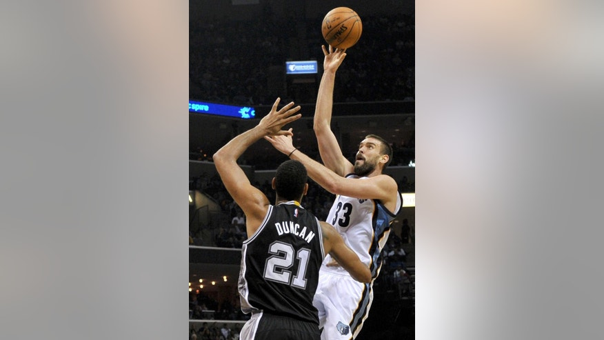 Memphis Grizzlies center Marc Gasol (33) shoots over San Antonio Spurs forward Tim Duncan (21) in the first half of an NBA basketball game Friday, Dec. 5, 2014, in Memphis, Tenn. (AP Photo/Brandon Dill)