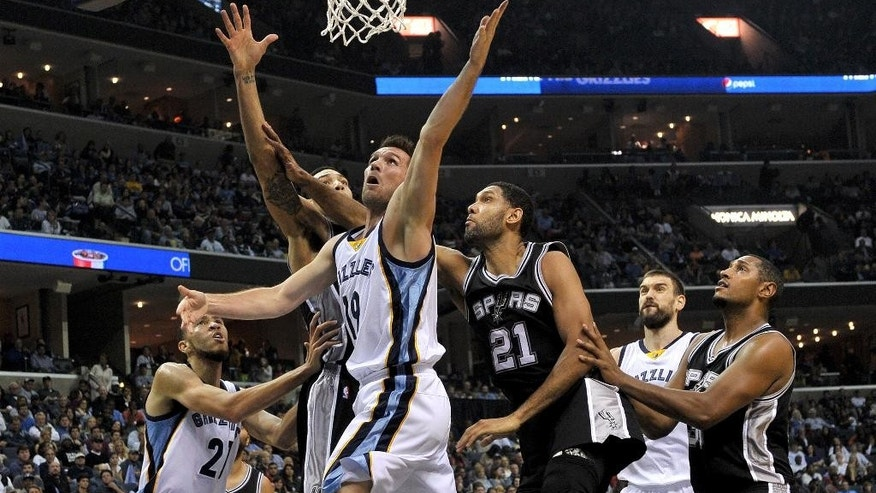 Memphis Grizzlies guard Beno Udrih (19) shoots past San Antonio Spurs guard Danny Green, left, forward Tim Duncan and forward Boris Diaw in the first half of an NBA basketball game Friday, Dec. 5, 2014, in Memphis, Tenn. (AP Photo/Brandon Dill)