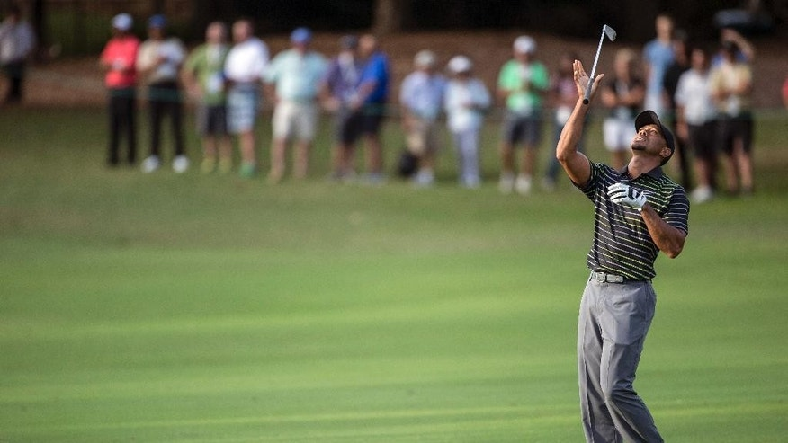 Tiger Woods tosses his club after over hitting on the 18th hole during the first round of the Hero World Challenge golf tournament, Thursday, Dec. 4, 2014, in Windermere, Fla. (AP Photo/Willie J. Allen Jr.)
