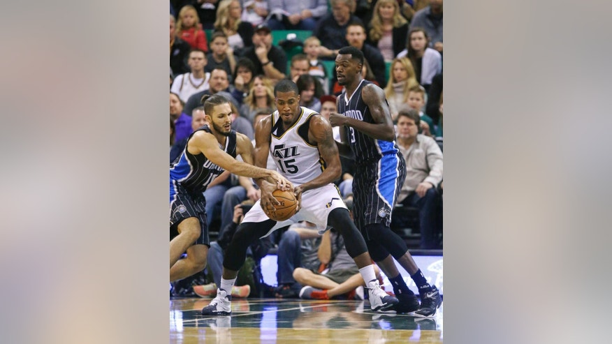 Orlando Magic's Evan Fournier, left, and Utah Jazz's Derrick Favors (15) battle for the ball as Magic's Dewayne Dedmon (3) looks on In the second quarter during an NBA basketball game Friday, Dec. 5, 2014, in Salt Lake City. (AP Photo/Rick Bowmer)
