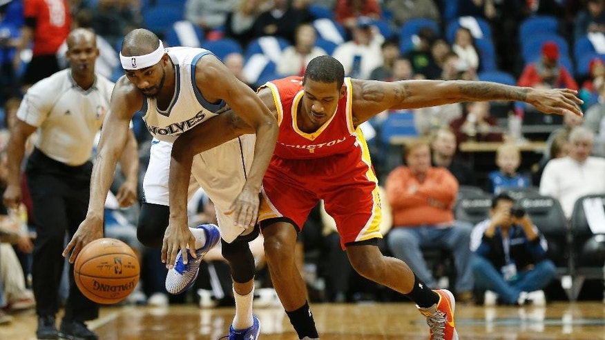 Minnesota Timberwolves forward Corey Brewer, left, steals the ball from Houston Rockets forward Trevor Ariza (1) during the first half of an NBA basketball game Friday, Dec, 5, 2014, in Minneapolis. (AP Photo/Stacy Bengs)