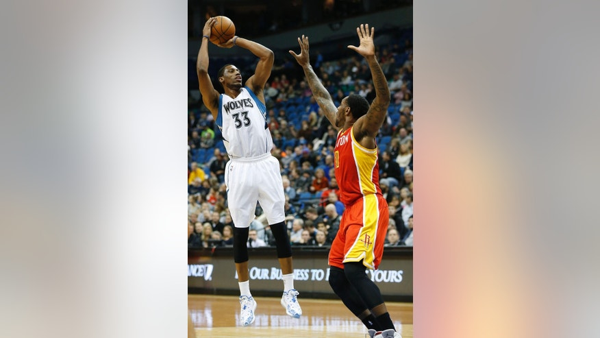 Minnesota Timberwolves forward Thaddeus Young (33) shoots against Houston Rockets center Tarik Black (10) during the first half of an NBA basketball game Friday, Dec, 5, 2014, in Minneapolis. (AP Photo/Stacy Bengs)