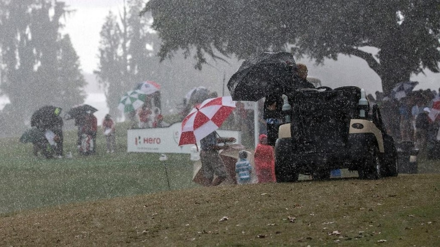 Tiger Woods and Patrick Reed, right, cover themselves with umbrellas on the 18th tee as an afternoon rainstorm stops play during the second round of the Hero World Challenge golf tournament on Friday, Dec. 5, 2014, in Windermere, Fla. (AP Photo/Willie J. Allen Jr.)
