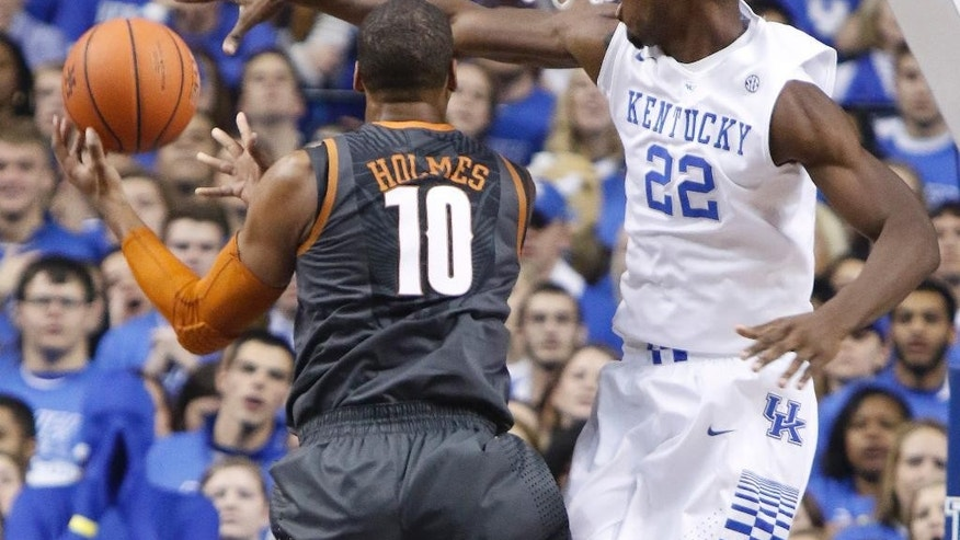 Texas' Jonathan Holmes (10) shoots under pressure from Kentucky's Alex Poythress (22) during the first half of an NCAA college basketball game, Friday, Dec. 5, 2014, in Lexington, Ky. (AP Photo/James Crisp)