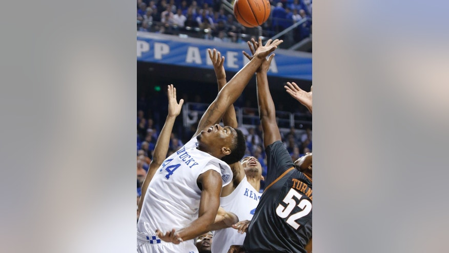 From left, Kentucky's Dakari Johnson, Trey Lyles and Texas' Myles Turner go after a rebound during the first half of an NCAA college basketball game, Friday, Dec. 5, 2014, in Lexington, Ky. (AP Photo/James Crisp)