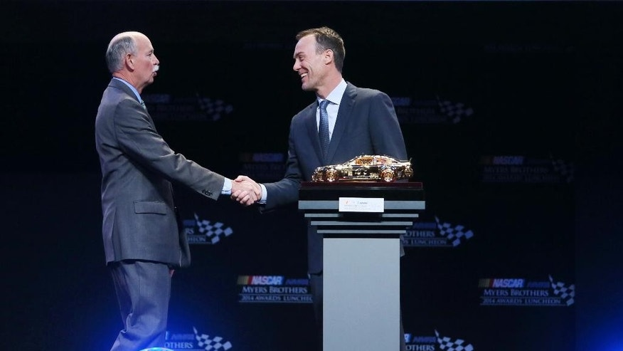 Stu Grant, left, general manager of Global Race Tires for Goodyear, shakes hand with NASCAR driver Kevin Harvick after announcing Harvick as the recipient of the Goodyear Tires Award during the NASCAR NMPA Myers Brothers Awards Luncheon Thursday, Dec. 4, 2014, in Las Vegas. NASCAR drivers are in Las Vegas for Champion's Week. (AP Photo/Ronda Churchill)