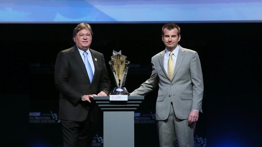 Robin Pemberton, left, senior vice president of Competition and Racing Development for NASCAR, and Rodney Childers pose for a photograph with Childers' Champion Crew Chief award during the NASCAR NMPA Myers Brothers 2014 Awards Luncheon Thursday, Dec. 4, 2014, in Las Vegas. NASCAR drivers are in town for Champion's Week. (AP Photo/Ronda Churchill)
