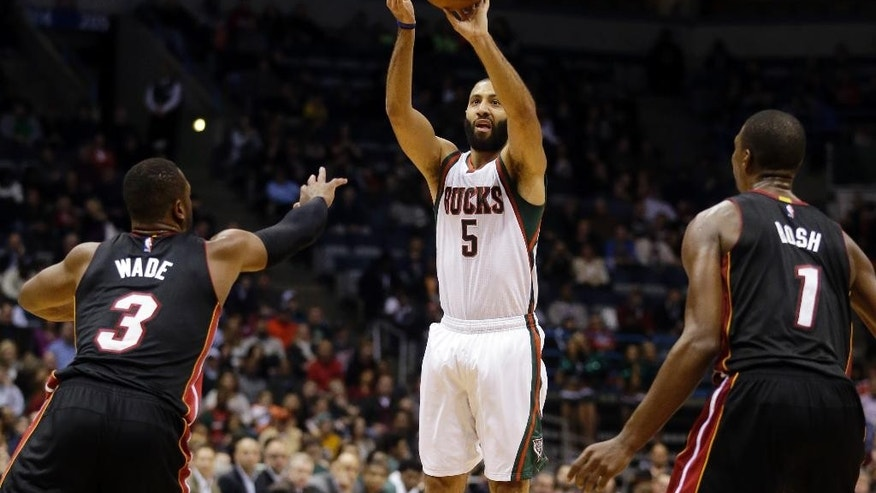 Milwaukee Bucks' Kendall Marshall shoot over Miami Heat's Chris Bosh (1) and Dwyane Wade (3) during the second half of an NBA basketball game Friday, Dec. 5, 2014, in Milwaukee. The Bucks won 109-85. (AP Photo/Morry Gash)
