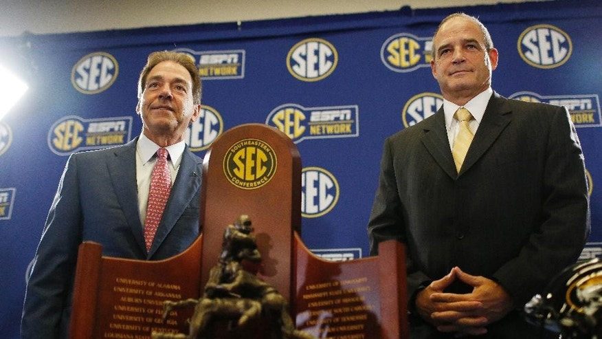 Alabama head coach Nick Saban, left, and Missouri head coach Gary Pinkel pose for photos Friday, Dec. 5, 2014, in Atlanta, ahead of the Southeastern Conference championship football game between Alabama and Missouri held Saturday. (AP Photo/Brynn Anderson)