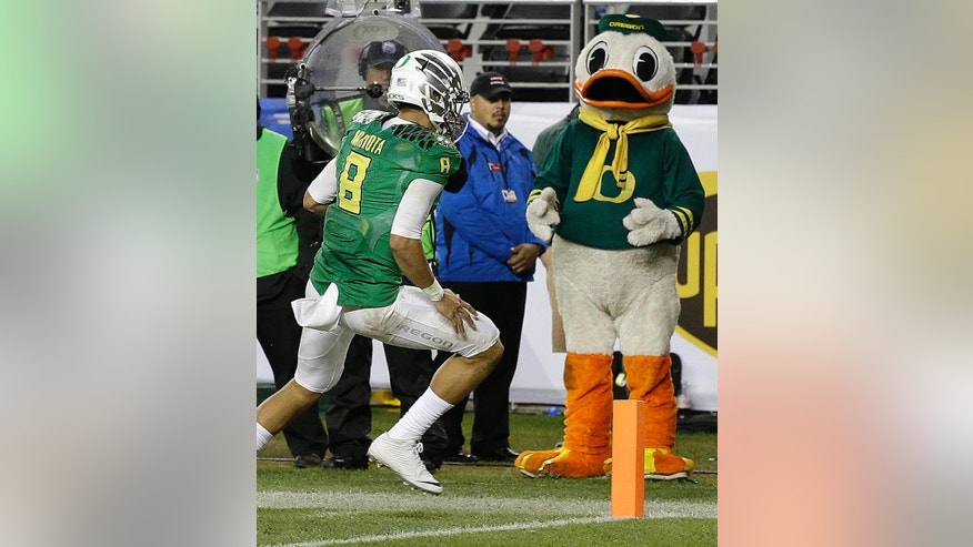 Oregon quarterback Marcus Mariota (8) scores against Arizona during the first half of a Pac-12 Conference championship NCAA college football game Friday, Dec. 5, 2014, in Santa Clara, Calif. (AP Photo/Ben Margot)