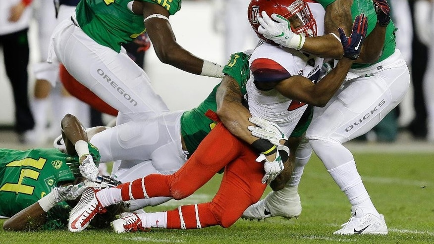 Arizona's Tyrell Johnson (2) fumbles the ball as he is tackled by Oregon's Ifo Ekpre-Olomu (14), Torrodney Prevot (86) and Erick Dargan (4) during the first half of a Pac-12 Conference championship NCAA college football game Friday, Dec. 5, 2014, in Santa Clara, Calif. (AP Photo/Ben Margot)