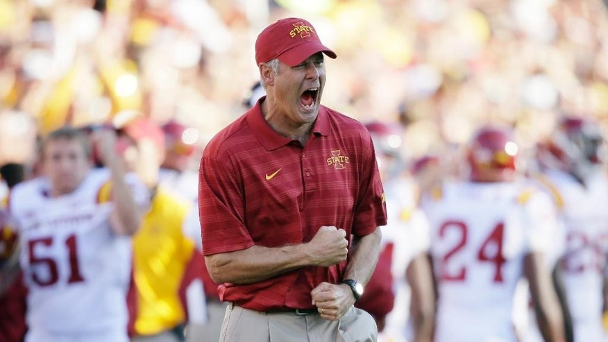 FILE - In this Sept. 13, 2014, file photo, Iowa State head coach Paul Rhoads reacts after a touchdown during the second half of an NCAA college football game against Iowa in Iowa City, Iowa. All signs indicate that Iowa State will give coach Rhoads another year to turn things around. The Cyclones appear headed for a 2-10 season and a winless Big 12 mark, but Roads believes the pieces are in place for improvement. (AP Photo/Charlie Neibergall, File)