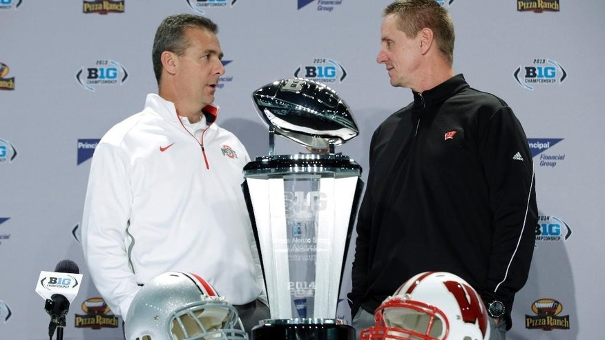 Wisconsin head coach Gary Anderson, right, talks with Ohio State head coach Urban Meyer during a news conference for the Big Ten Conference championship NCAA college football game Friday, Dec. 5, 2014, in Indianapolis. Ohio State will play Wisconsin,  Saturday for the championship. (AP Photo/Darron Cummings)
