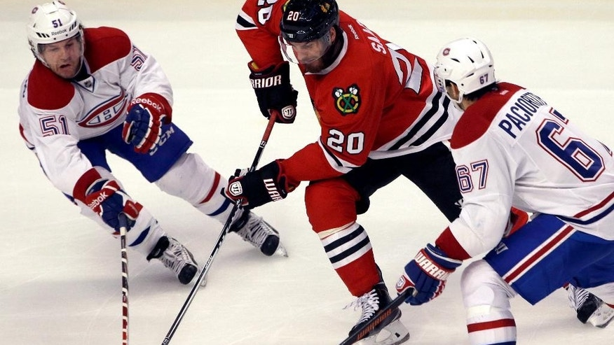 Chicago Blackhawks left wing Brandon Saad (20) controls the puck against Montreal Canadiens center David Desharnais (51) and left wing Max Pacioretty (67) during the third period of an NHL hockey game in Chicago, Friday, Dec. 5, 2014. The Blackhawks won 4-3. (AP Photo/Nam Y. Huh)