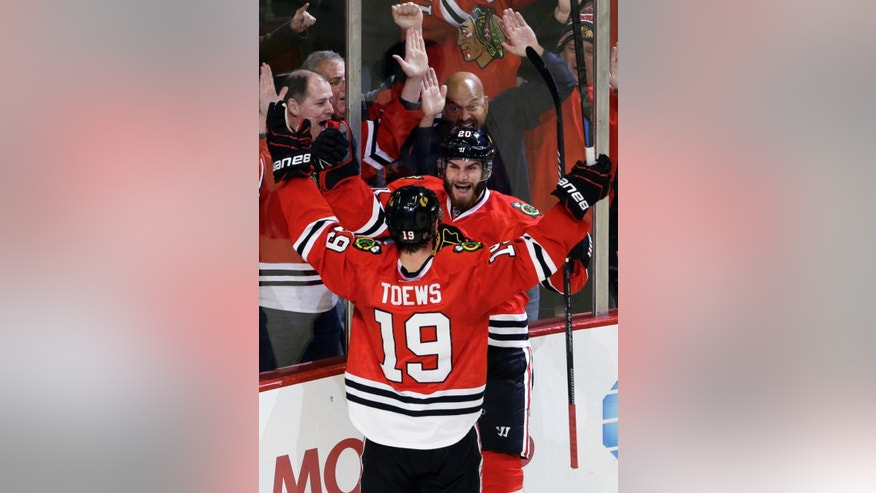 Chicago Blackhawks left wing Brandon Saad (20) celebrates with center Jonathan Toews 919) after scoring his goal during the third period of an NHL hockey game against Montreal Canadiens in Chicago, Friday, Dec. 5, 2014. The Blackhawks won 4-3. (AP Photo/Nam Y. Huh)