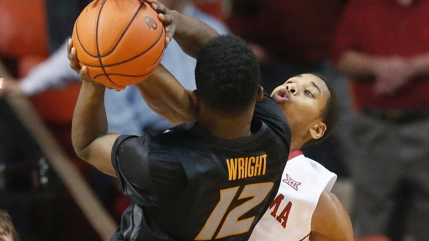 Oklahoma guard Isaiah Cousins, right, gets his hand on the ball as Missouri guard Namon Wright (12) shoots in the first half of an NCAA college basketball game in Norman, Okla., Friday, Dec. 5, 2014. (AP Photo/Sue Ogrocki)