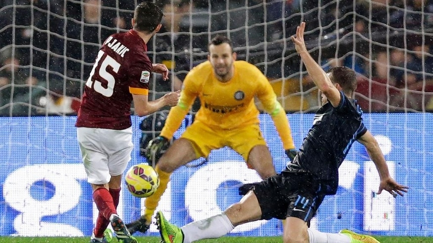 Roma's Miralem Pjanic, left, scores during a Serie A soccer match between Roma and Inter Milan at Rome's Olympic Stadium, Sunday, Nov. 30, 2014. (AP Photo/Andrew Medichini)