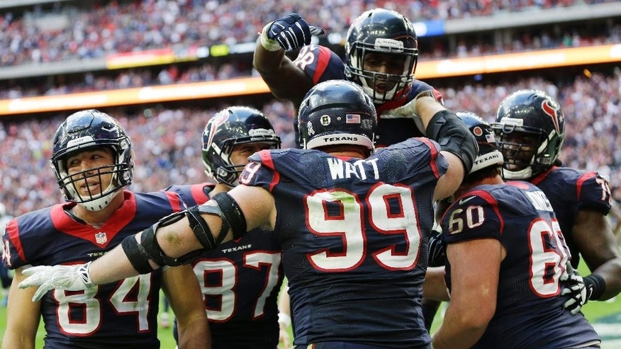 Houston Texans' J.J. Watt (99) celebrates his touchdown reception with teammate during the second half of an NFL football game against the Tennessee Titans Sunday, Nov. 30, 2014, in Houston. (AP Photo/David J. Phillip)