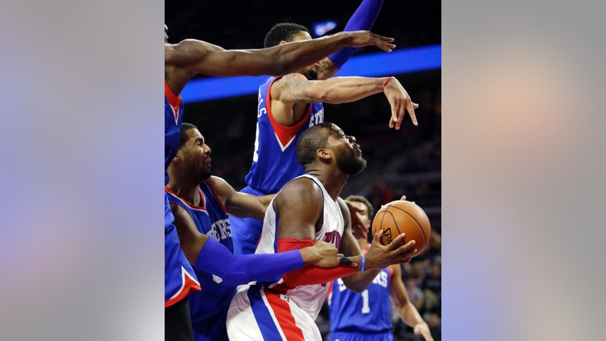 Detroit Pistons forward Greg Monroe, front right, is fouled by Philadelphia 76ers forward Brandon Davies, left, as 76ers guard K.J. McDaniels towers above during the first half of an NBA basketball game in Auburn Hills, Mich., Saturday, Dec. 6, 2014. (AP Photo/Carlos Osorio)