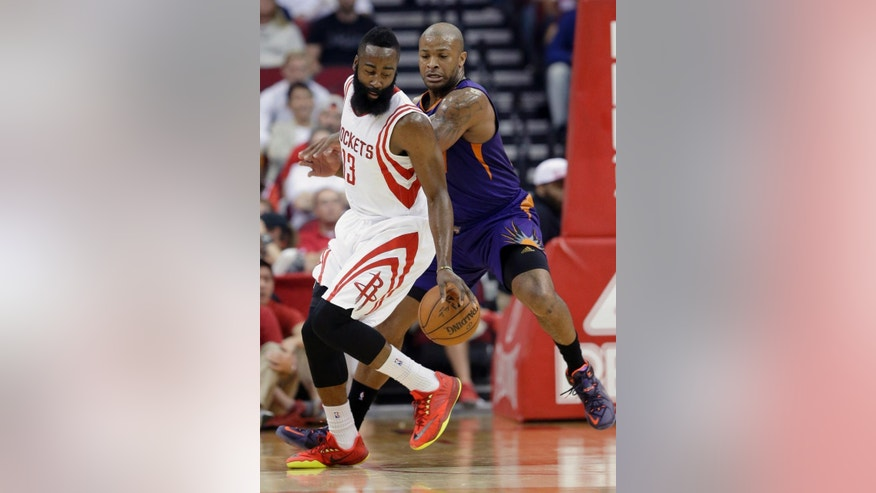 Houston Rockets' James Harden (13) works to maintain control of the ball under pressure from Phoenix Suns' P.J. Tucker in the first half of an NBA basketball game Saturday, Dec. 6, 2014, in Houston. (AP Photo/Pat Sullivan)