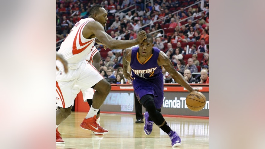 Houston Rockets' Tarik Black, left, tries to slow down Phoenix Suns' Eric Bledsoe (2) in the first half of an NBA basketball game Saturday, Dec. 6, 2014, in Houston. (AP Photo/Pat Sullivan)