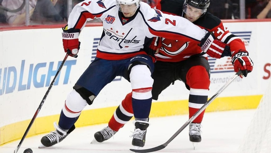 Washington Capitals defenseman Matt Niskanen, left, skates against New Jersey Devils right wing Mike Sislo during the second period of an NHL hockey game, Saturday, Dec. 6, 2014, in Newark, N.J. (AP Photo/Julio Cortez)