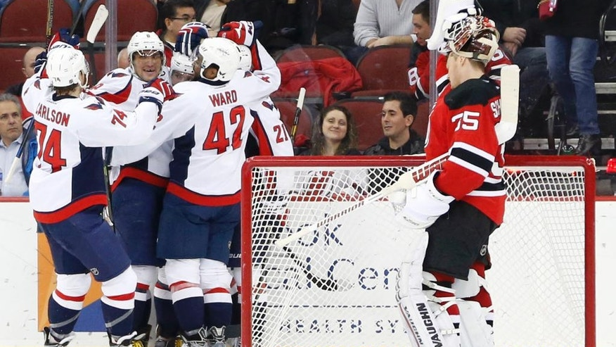 Washington Capitals players, left, celebrate a goal by teammate Evgeny Kuznetsov, of Russia, against the New Jersey Devils during the second period of an NHL hockey game, Saturday, Dec. 6, 2014, in Newark, N.J. (AP Photo/Julio Cortez)