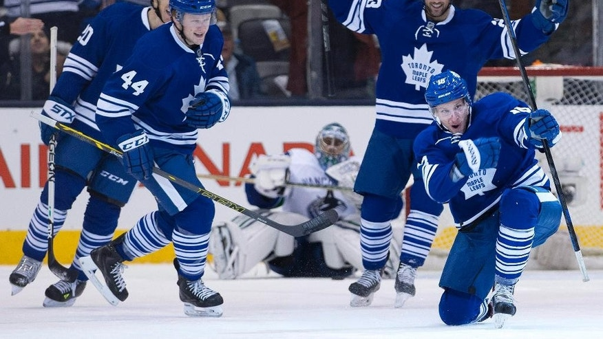 Toronto Maple Leafs forward Richard Panik, bottom right, celebrates his goal with teammates against the Vancouver Canucks during first period NHL hockey action in Toronto on Saturday, Dec. 6, 2014.   (AP Photo/The Canadian Press, Nathan Denette