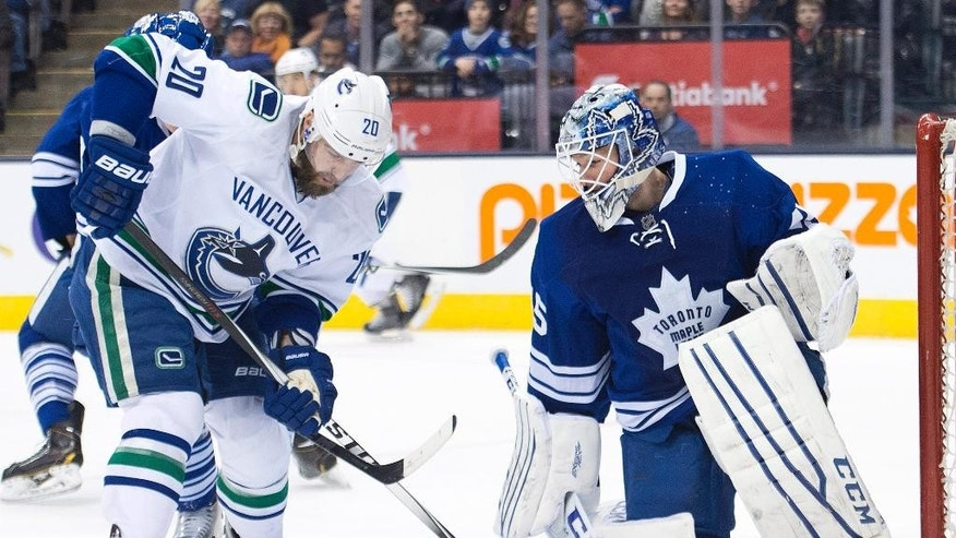 Toronto Maple Leafs goalie Jonathan Bernier, right, makes a save against Vancouver Canucks forward Chris Higgins (20) during first period NHL hockey action in Toronto on Saturday, Dec. 6, 2014.   (AP Photo/The Canadian Press, Nathan Denette