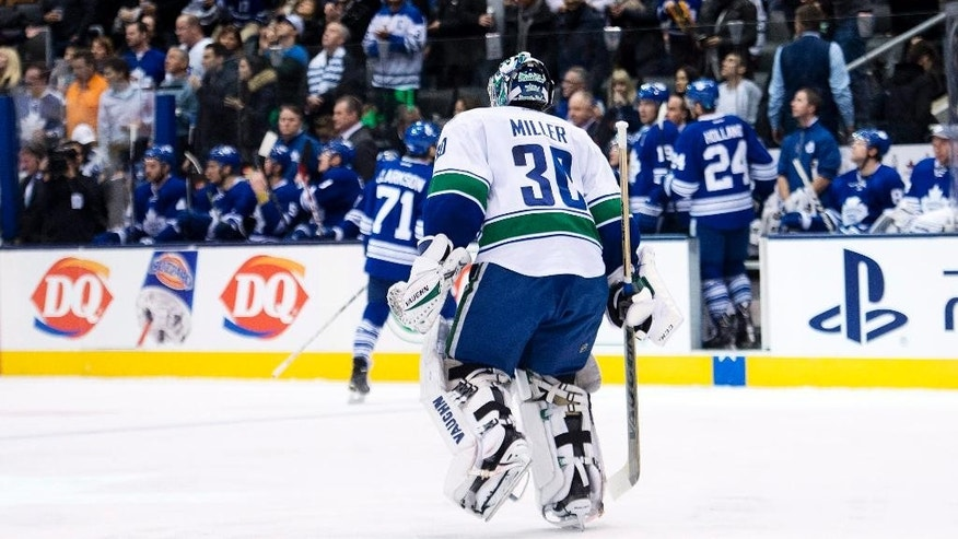 Vancouver Canucks goalie Ryan Miller (30) skates to his bench after being pulled against the Toronto Maple Leafs during second period NHL hockey action in Toronto on Saturday, Dec. 6, 2014. (AP Photo/The Canadian Press, Nathan Denette)
