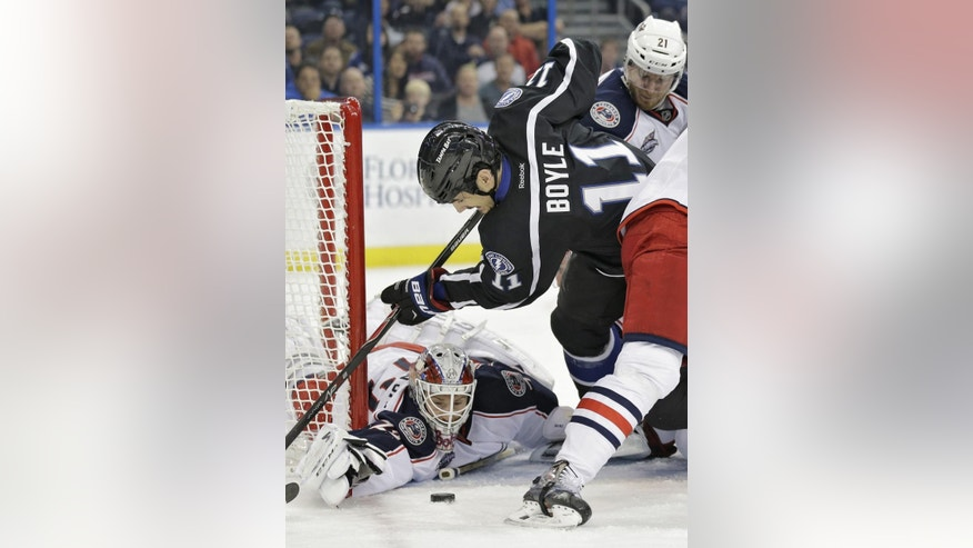 Columbus Blue Jackets goalie Sergei Bobrovsky (72), of Russia, goes for the puck as defenseman James Wisniewski (21) holds up Tampa Bay Lightning center Brian Boyle (11) during the second period of an NHL hockey game Saturday, Dec. 6, 2014, in Tampa, Fla. (AP Photo/Chris O'Meara)