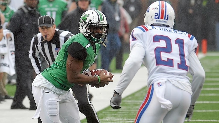 Marshall's Tommy Shuler (1) looks for running room as Louisiana Tech Adairius Barnes (21) closes in during the Conference USA championship NCAA college football game in Huntington, W.Va., Saturday Dec. 6, 2014. (AP Photo/Chris Tilley)