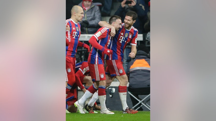 Bayern's Franck Ribery from France, center, celebrates with teammate Bayern's Xabi Alonso from Spain, right, after scoring his side's opening goal during the German first division Bundesliga soccer match between FC Bayern and Bayer Leverkusen 04 in the Allianz Arena in Munich, Germany, on Saturday, Dec. 6, 2014. (AP Photo/Matthias Schrader)
