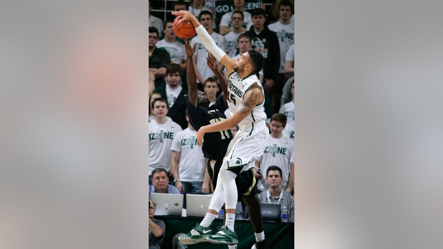 Michigan State's Denzel Valentine, right, blocks a shot by Arkansas-Pine Bluff's Tevin Hammond during the first half of an NCAA college basketball game, Saturday, Dec. 6, 2014, in East Lansing, Mich. (AP Photo/Al Goldis)