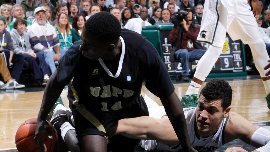 Arkansas-Pine Bluff's Tevin Hammond, left, and Michigan State's Gavin Schilling battle for a loose ball during the first half of an NCAA college basketball game, Saturday, Dec. 6, 2014, in East Lansing, Mich. (AP Photo/Al Goldis)