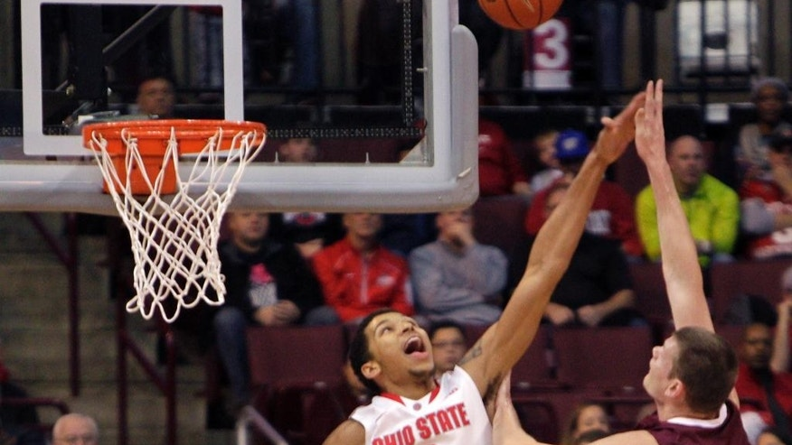 Colgate's Ethan Jacobs, right, shoots over Ohio State's Marc Loving during the first half of an NCAA college basketball game Saturday, Dec. 6, 2014, in Columbus, Ohio. (AP Photo/Jay LaPrete)